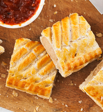 Sausage rolls on a wooden chopping board with a tomato salsa