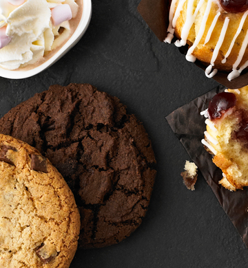 A selection of cakes, biscuits and hot drinks