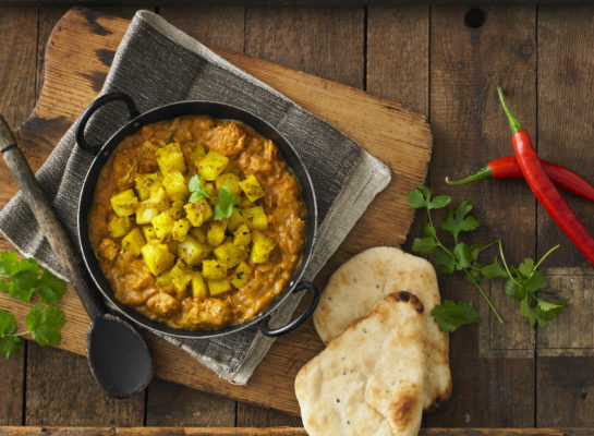 A delicious looking curry with chilli peppers, fresh coriander and naan